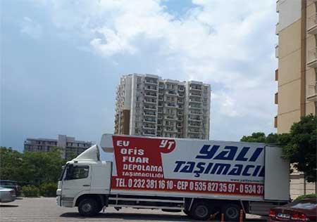 Karşıyaka nakliyat firmaları başlığı için kullanılan görselde, Yalı Nakliyat firmamıza ait geniş kamyon, müşterimizin eşyalarını taşımak üzere binanın önüne park etmiş.
