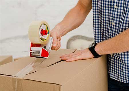 Karşıyaka nakliyat hizmetleri için kullanılan görselde, Yalı Nakliyat firma çalışanımız, müşterimizin eşyalarını kutunun için yerleştirip kutuyu bantla kapatıyor.